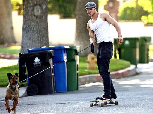 Slutz skateboarding with his dog Kola.